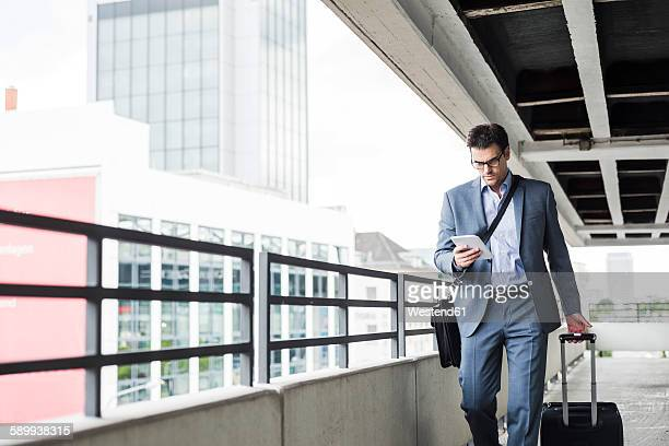 Businessman on business trip looking at his mini tablet