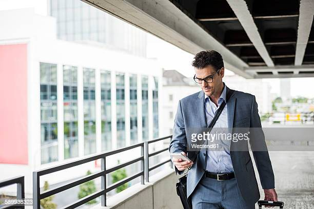 Businessman on business trip looking at his smartphone
