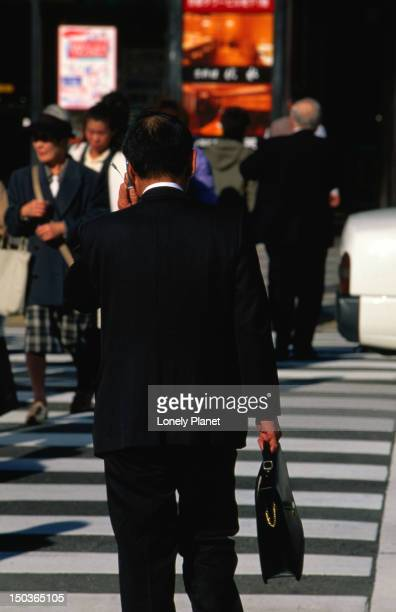 Businessman on cell phone crossing road.