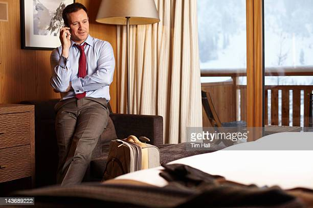 Businessman on cell phone in hotel room