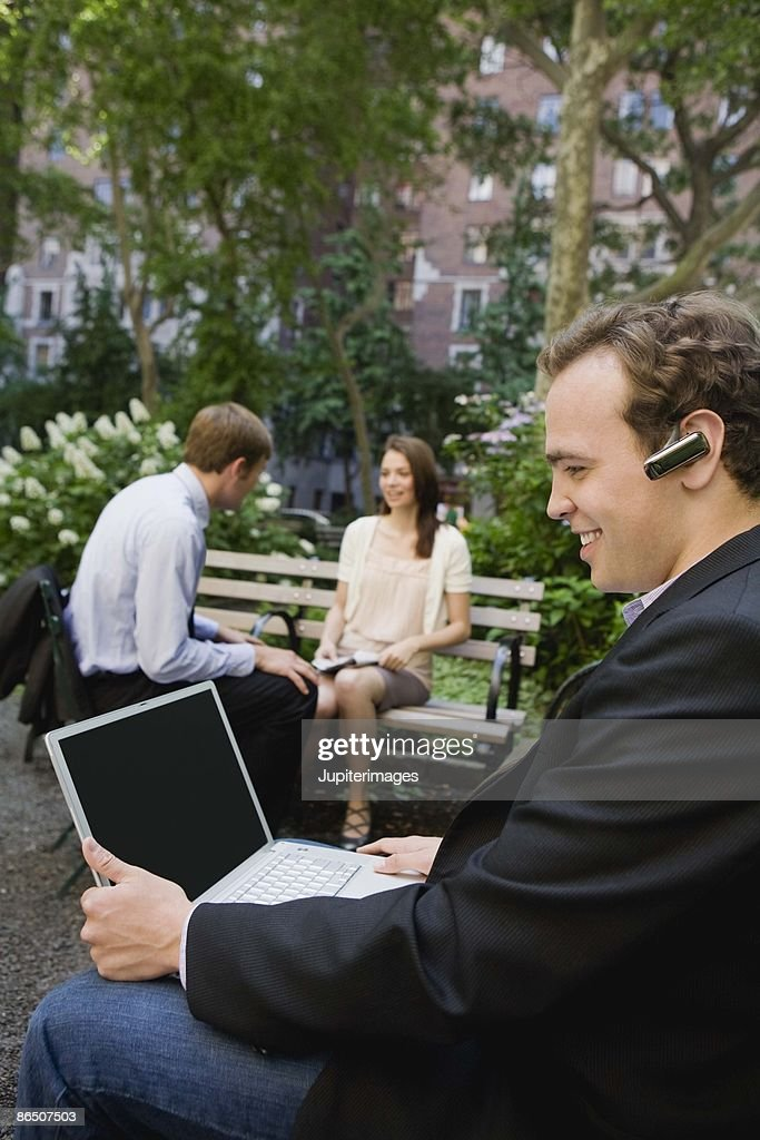 Businessman on cell phone in park, New York City : Stock Photo