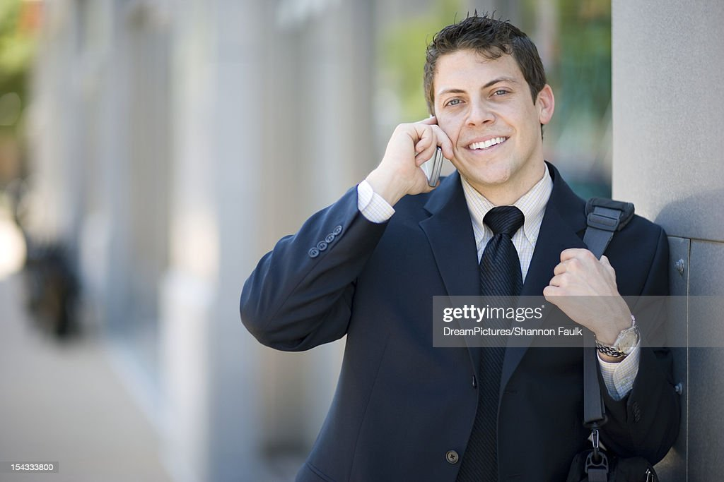 Businessman on cell phone outside : Stock Photo