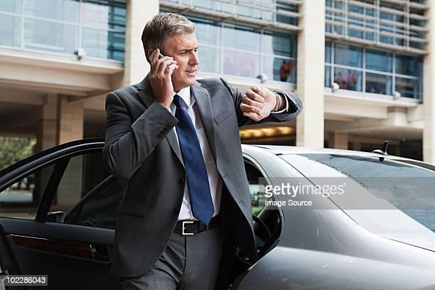 Geschäftsmann auf cellphone Blick in die Uhr