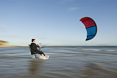 Businessman on chair, pulled by surfing kite in sea