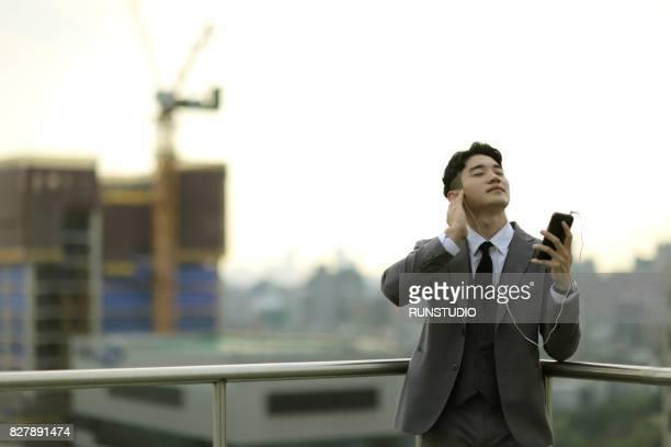 businessman on city rooftop listening to music on headphones