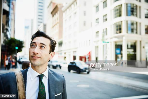 Businessman on downtown street looking at city skyline