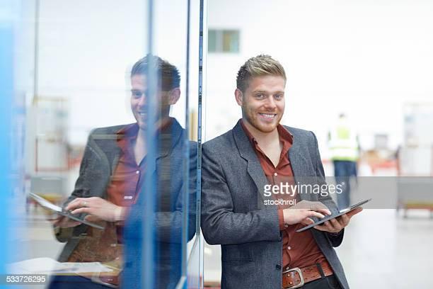 Businessman on factory shopfloor with digital tablet