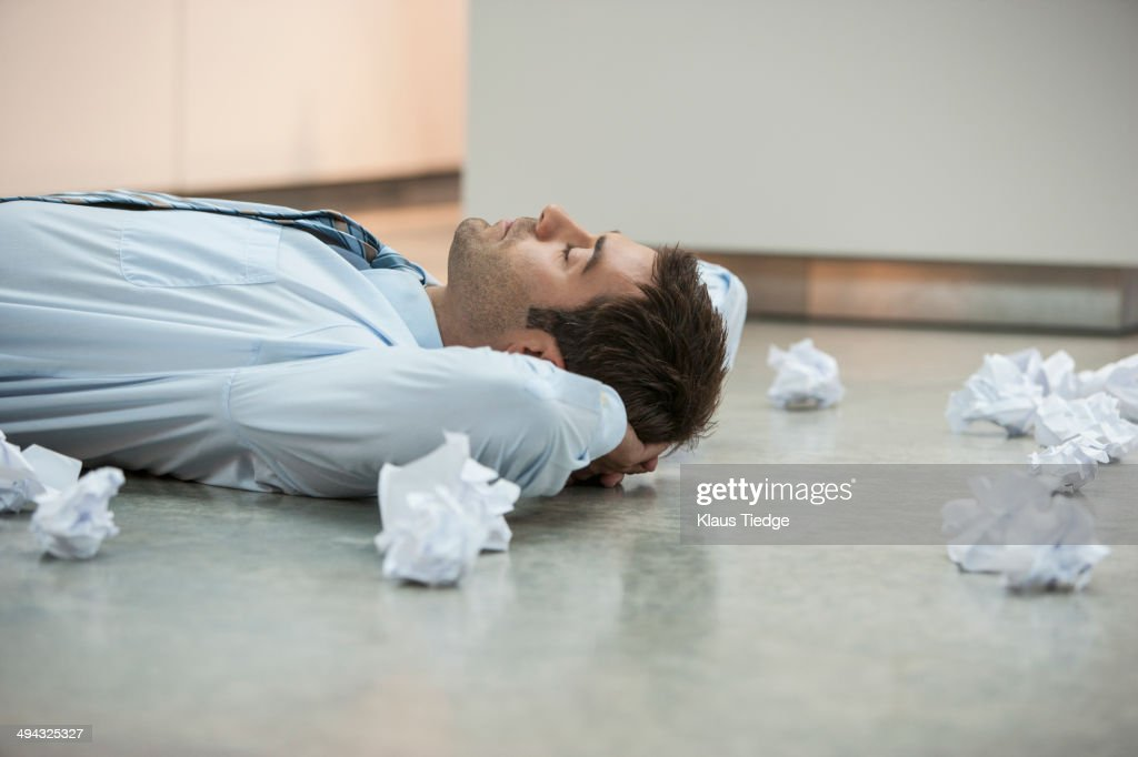 Businessman on floor surrounded by crumpled paper : Stock Photo