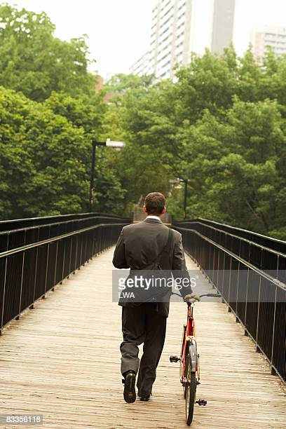 Businessman on foot bridge with bicycle