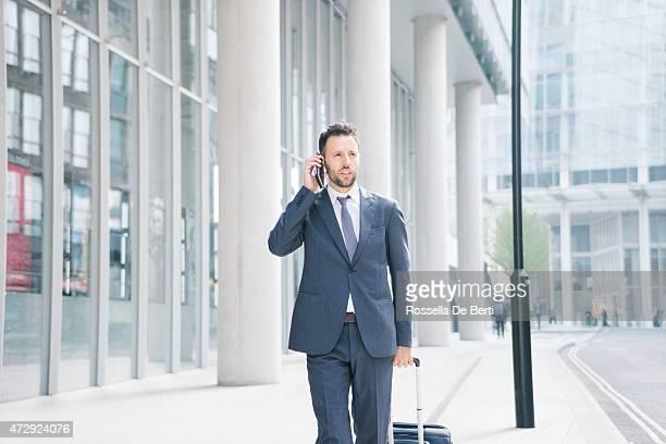 Empresario en su teléfono celular con maleta