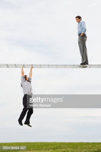 Businessman on horizontal ladder watching businessman suspended below : Stock Photo