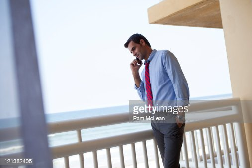 Businessman on hotel balcony overlooking ocean stock photo for Balcony overlooking ocean