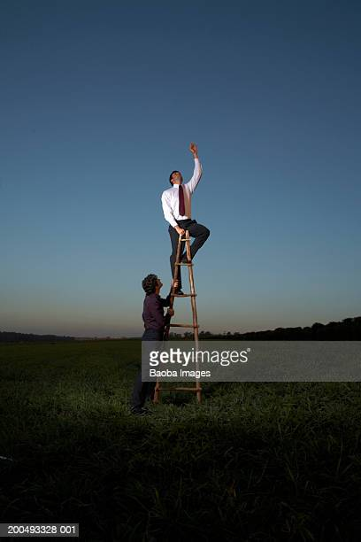 Businessman on ladder in empty field reaching, man giving support