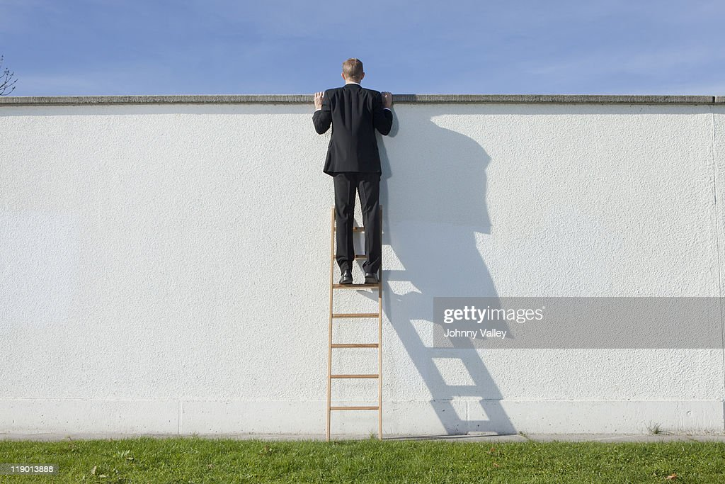 Businessman on ladder looking over wall : Stock Photo