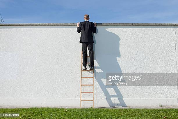 Businessman on ladder looking over wall