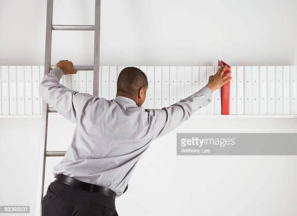 Businessman on ladder removing binder from shelf