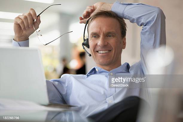 Businessman on laptop and earpiece