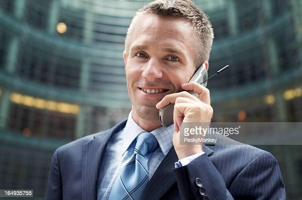 ビジネスマンが携帯電話のカメラに笑う