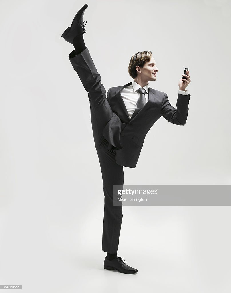 Businessman on one leg looking at mobile : Stock Photo
