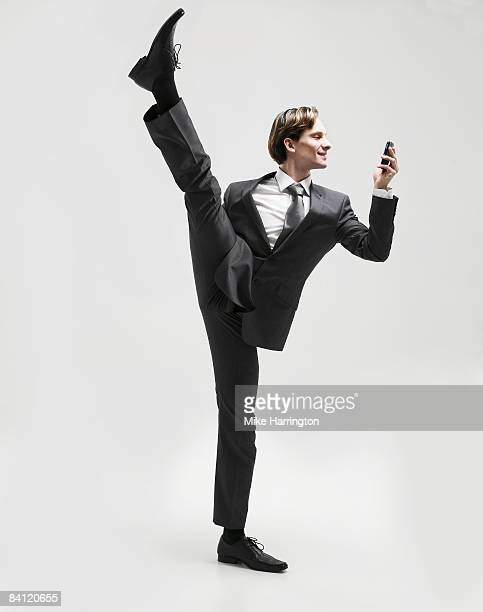 Businessman on one leg looking at mobile
