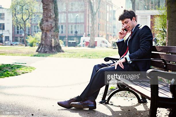 Businessman on park bench on cell phone