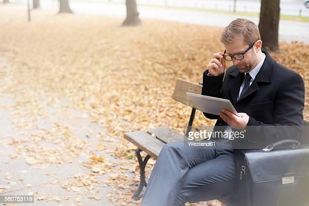 Businessman on park bench using digital tablet