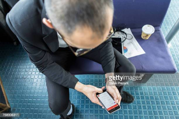 Businessman on passenger ferry looking at smartphone