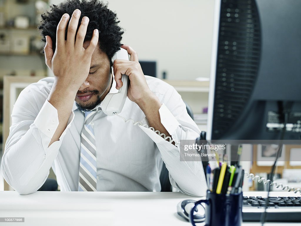Businessman on phone at desk hand on forehead : Stock Photo