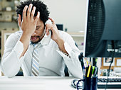 Businessman on phone at desk hand on forehead