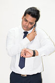 Indian businessman talking on smart phone and checking the time