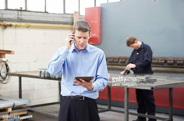 Hombre de negocios con teléfono en fábrica Fabricación en acero