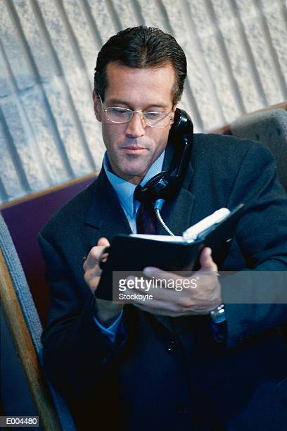 Businessman on phone looking at daytimer