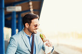 Young businessman is eating sandwich while waiting train.