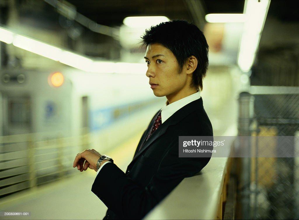 Businessman on railway platform, side view