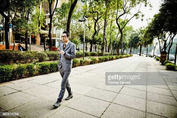 Businessman on sidewalk looking at smartphone