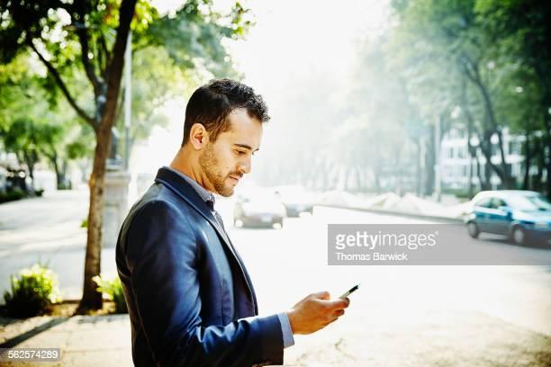 Businessman on sidewalk looking at smartphone