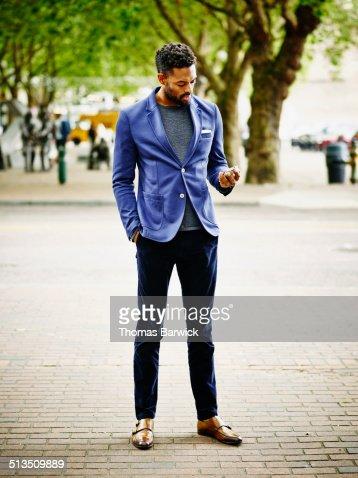 Businessman on sidewalk working on smart phone