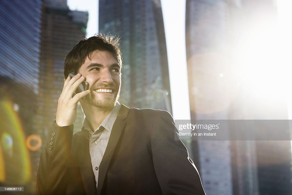 Businessman on smartphone in the city : Stock Photo
