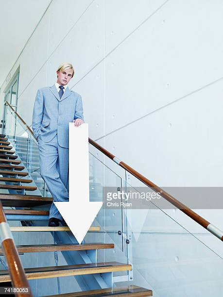 Businessman on stairs with blank arrow pointing down