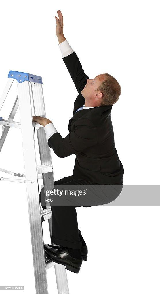 Businessman on step ladder