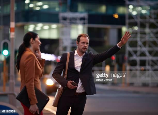 Businessman on street hailing cab, at night