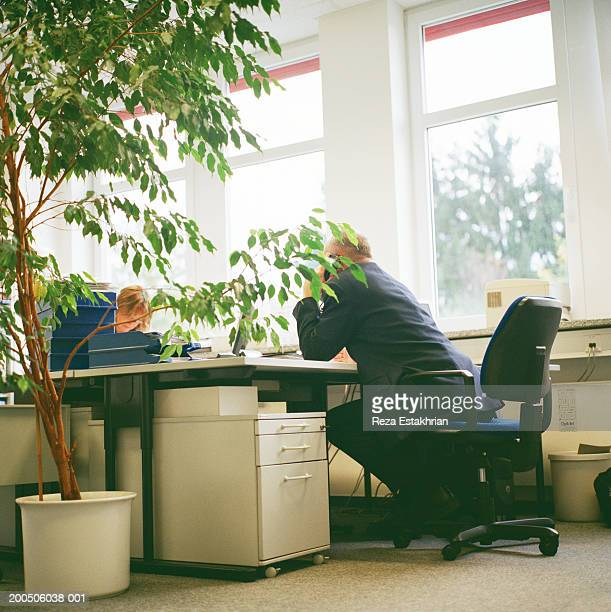 Businessman on telephone leaning forward at desk