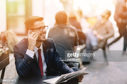 Businessman on the phone at a sidewalk cafe
