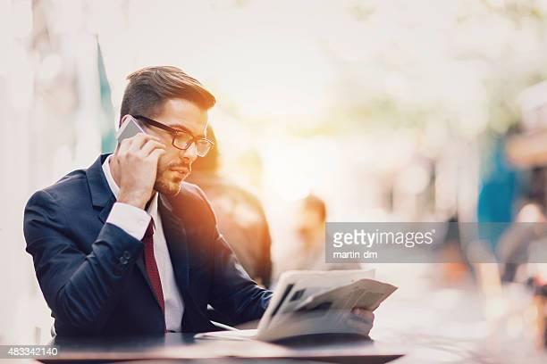 Homme d'affaires sur le téléphone dans une terrasse de café
