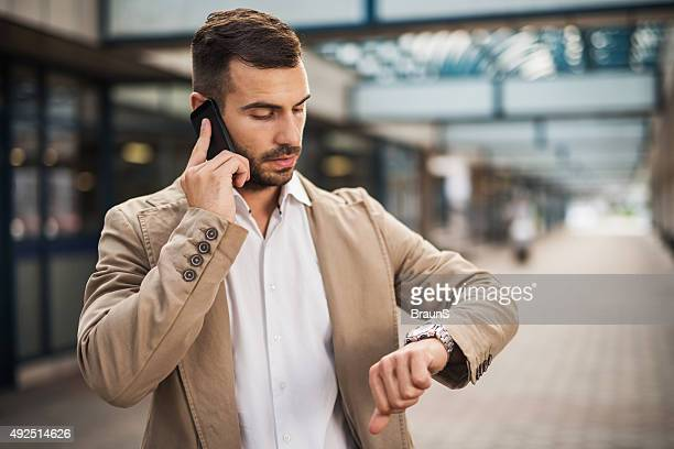 Businessman on the phone checking the time.