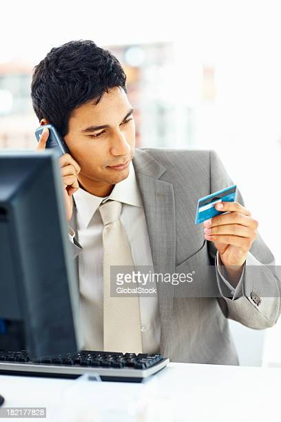 Businessman on the phone holding his credit card
