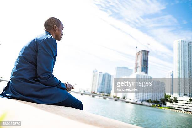 businessman on the phone in miami sitting on the park