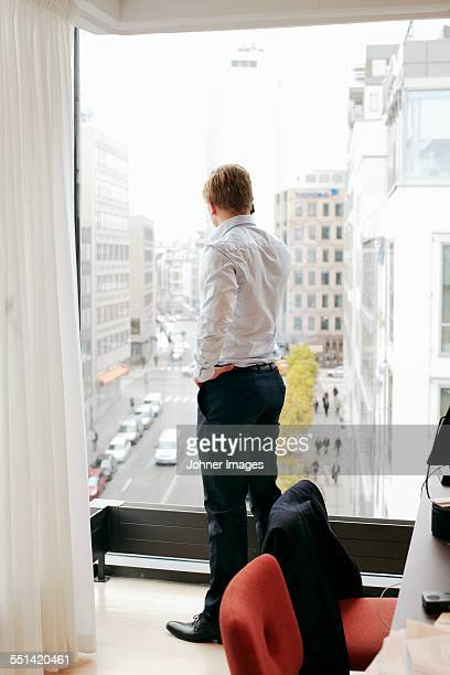 Businessman on the phone in office looking through window