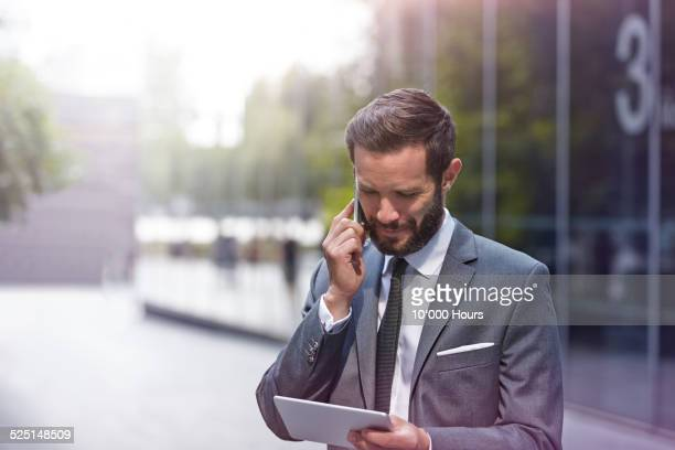 A Businessman on the phone looking at an iPad