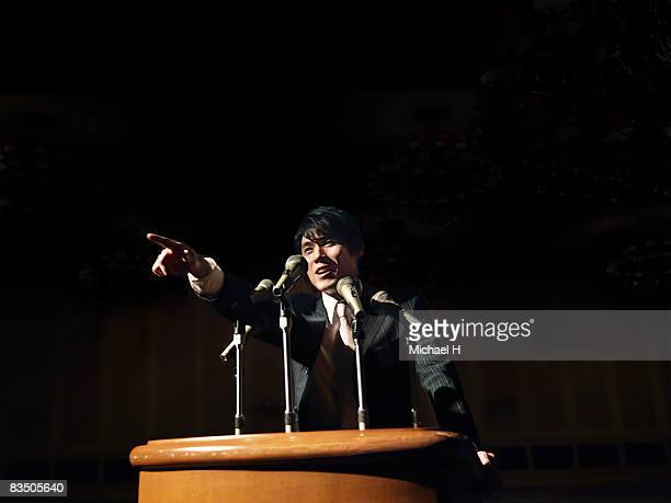 Businessman on the speach stand, pointing